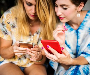 Two females on mobile phones texting